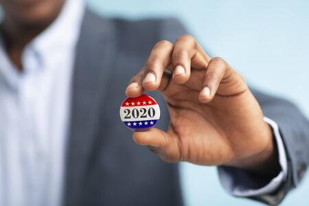African businessman holding Vote button for Presidential election 2020 in America, blurred background