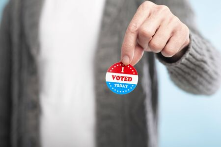 Hand of man holding an I voted today sticker with American Flag, blurred background
