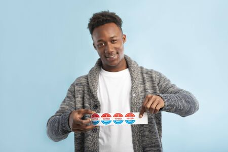 Happy african american man holding roll with stickers for people who voted on president elections 2020 in USA 版權商用圖片