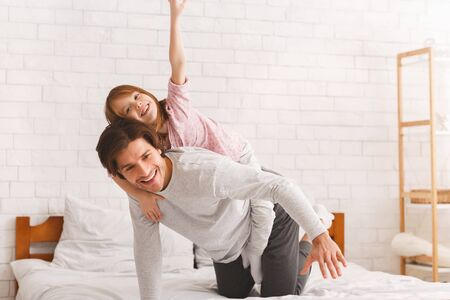Preschool girl playing with her father in bed at home, sitting on his back, copy space