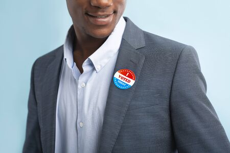 Man putting on Vote button for Presidential election 2020 in America on blue background