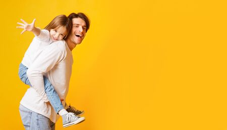 Positive dad holding his happy daughter on his back, imitating airplane, yellow background, panorama with empty space