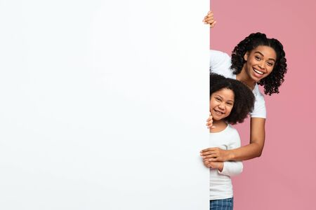 Family Offer. Happy African American Mother And Preschool Daughter Peeking Out Of Blank White Board With Free Space For Your Ad Over Pink Background