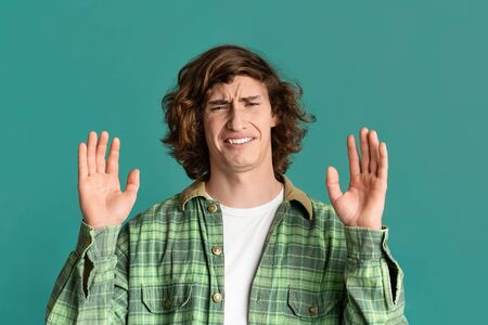 Millennial guy with disgusted face showing denial gesture on turquoise background Foto de archivo
