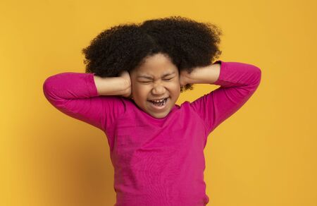 Annoyed little african girl covering ears with hands, doesnt want to hear or know something, emotionally reacting to arguing, yellow background