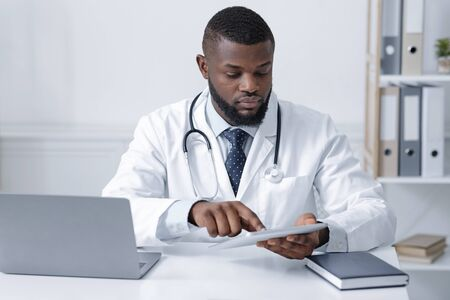 Concentrated black doctor using digital tablet at his office for online consultation during quarantine