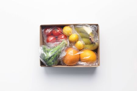 Safety delivery. Home delivery food during virus outbreak, fresh fruits and vegetables in cardboard box on white background Stock Photo