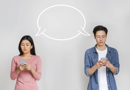 Asian couple having fun while isolation, chatting via new mobile application, grey studio background, empty communication bubble between man and woman