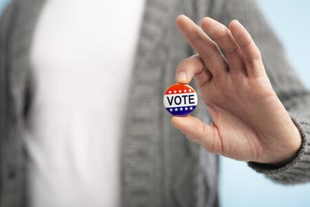 American elections concept 2020. Man with vote pin in hand on blurred background