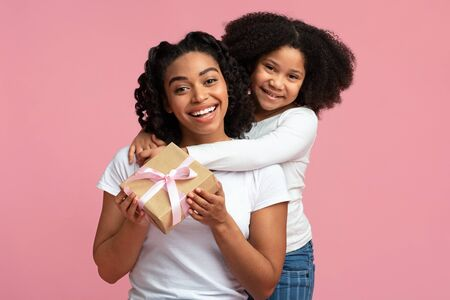 Happy Mothers Day.Happy Black Woman Received Gift From Her Adorable Little Daughter, Embracing And Smiling To Camera, Isolated On Pink Background Stockfoto