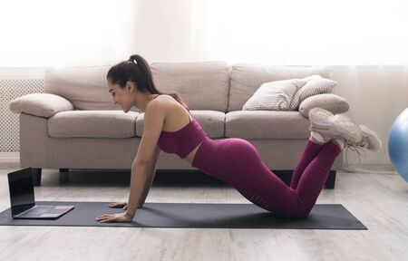 Sports during home isolation. Young girl doing exercises in front of laptop with empty screen, space for design