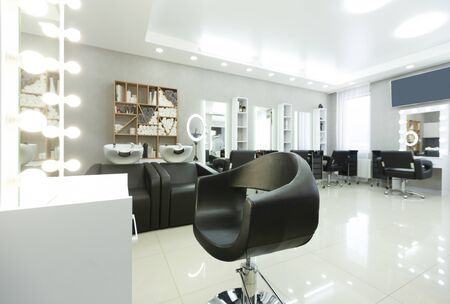Barber chair and backlit mirror in bright Interior, free space Stock Photo