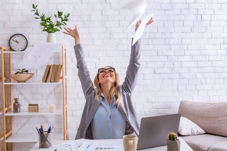 Happy girl throws up documents at workplace, at home