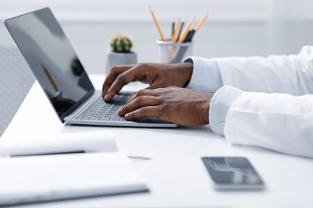 African american doctor hands working with laptop, office interior, close up