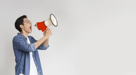Attention. Emotional asian young man using loudspeaker over grey studio background, panorama with copy space