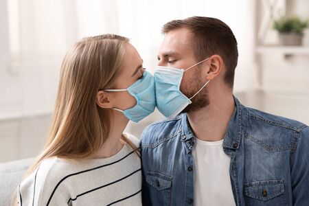 Quarantine romance. Couple in love kissing in protective medical masks at home