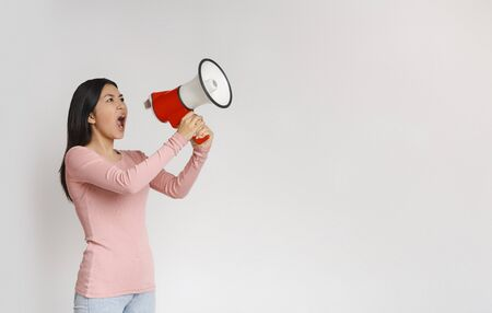 Stay at home. Agressive asian girl screaming towards copy space over grey background, using megaphone