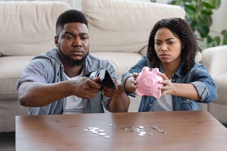 Financial Crisis Concept. Concerned Black Couple Suffering From Poverty During Quarantine, Holding Empty Wallet And Piggy Bank, Counting Coins Stock Photo