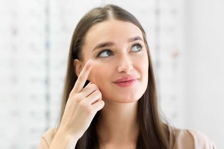 How To Apply Contact Lenses Concept. Close up portrait of young woman wearing eye lens, looking aside