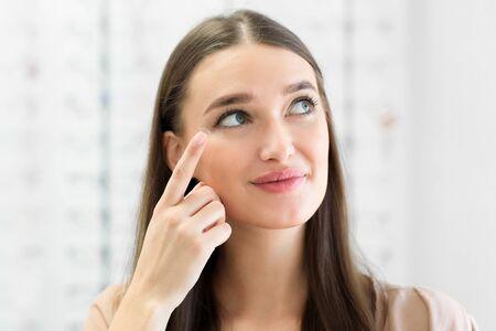 So wenden Sie das Kontaktlinsen-Konzept an. Nahaufnahme Porträt der jungen Frau mit Augenlinse, beiseite schauen