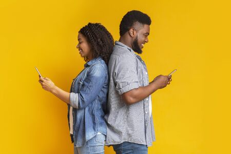 Social Network Addiction. Black Millennial Couple Using Smartphones, Standing Back To Back And Ignoring Each Other, Yellow Background