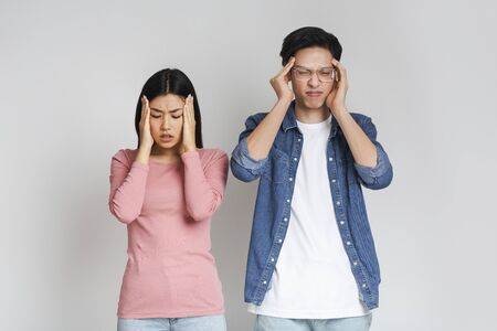 Got sick. Asian sad couple having headache, touching their temples over grey background