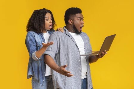 Shock content. African american couple holding laptop and emotionally reacting to news in internet, looking at computer screen with open mouth Reklamní fotografie
