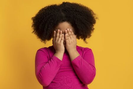 Portrait of little african amertican girl crying and covering her eyes with hands, feeling scared and lonely, standing over yellow background