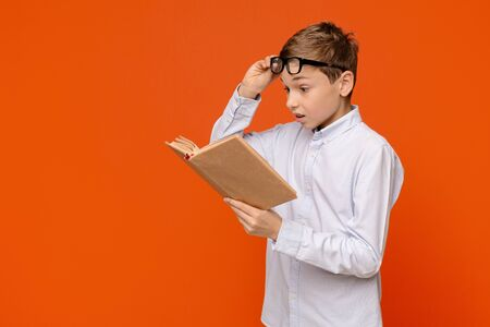 Emotional teenager reading exciting book, raising his glasses in amazement, orange panorama background with free space