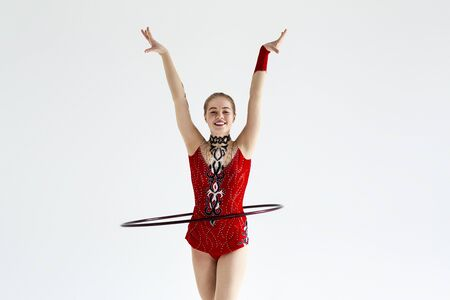 Artistic young gymnast in red leotard performing with hoop, isolated on white