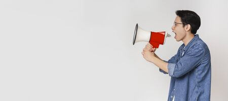 Agressive asian guy shouting in megaphone towards copy space over grey studio background, panorama