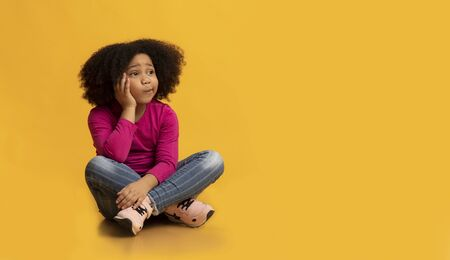 Pensive little black girl sitting on floor over yellow background in studio and thinking, looking away at copy space, panorama