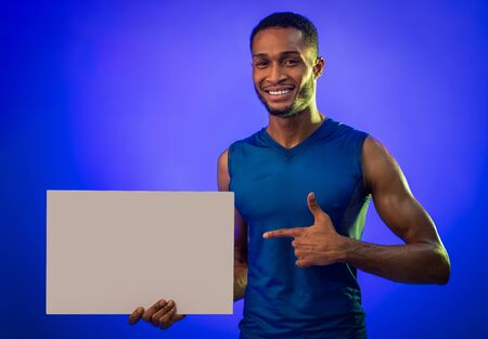 Workout Concept. Fit Man Holding Empty White Poster Pointing Finger At It Advertising Gym Over Blue Background. Studio Shot, Mockup