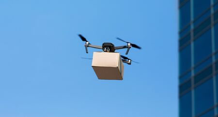 Fast and contactless delivery while quarantine. Modern drone delivering cardboard box, panorama, copy space