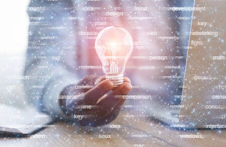 New idea concept. Unrecognizable black programmer holding illuminated light bulb in hand while sitting at workplace Banque d'images
