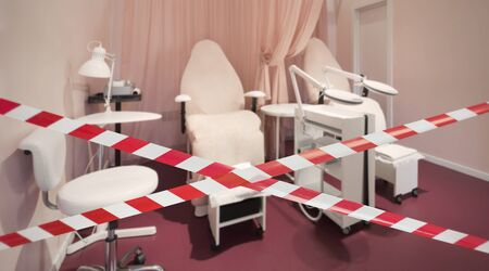 Quarantine Zone Warning Tape, Do Not Cross. Red and white hazard safety stripes across closed beauty salon pedicure spa