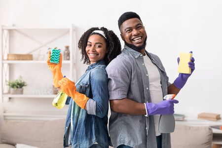 Portrait of cheerful afro couple posing with cleaning supplies while doing housework together, holding sponges and detergent sprayers, free space