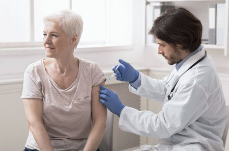 Annual vaccination. Doctor injecting vaccine to senior woman at clinic