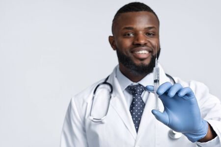 Vacination during quarantine. Smiling african male doctor holding an injection over white background, copy space