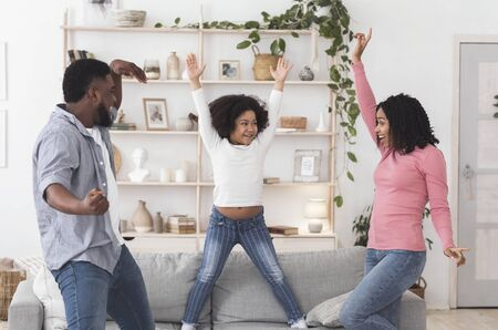 Joyful black family of three dancing dancing together at home, raising arms and laughing in living room