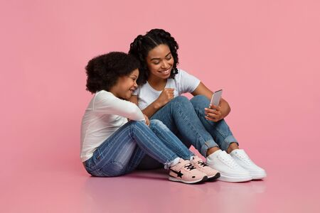 Smiling african girl and her mom sitting on floor with smartphone, watching video or cartoons from internet, free space Stock Photo