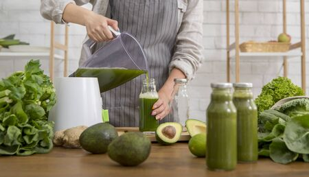 Take-away smoothie. Woman in linen apron pouring smoothie drink from blender to bottle surrounded with vegetables and greens, panorama Stok Fotoğraf