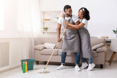 Happy black couple doing household chores together, mopping floor and hugging, spring-cleaning their apartment Stock Photo