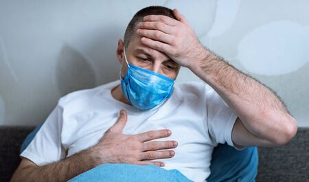 Covid-19 Symptoms. Sick Man Having Fever And Breathing Difficulty Wearing Medical Mask Sitting In Bed At Home Stock Photo