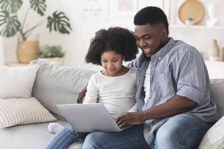 Happy African Father And His Little Daughter Using Laptop At Home Together, Resting On Sofa, Watching Movies Online Or Browsing Internet Stock fotó