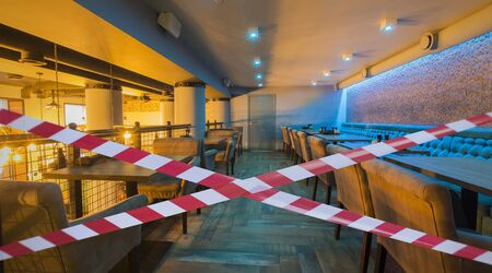 Quarantine Zone Warning Tape, Do Not Cross Concept. Red and white hazard safety stripes across empty closed loft bar Stock Photo