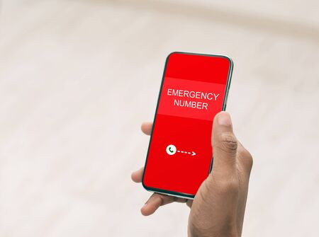 Top view over shoulder of hand holding smart phone with emergency number on red screen over blurred background
