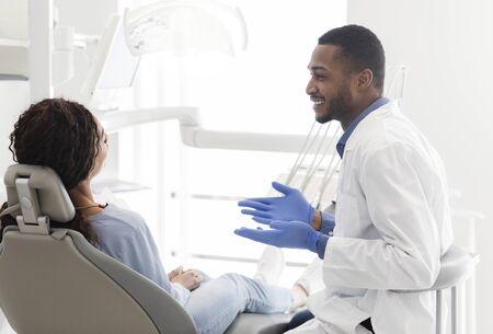 Friendly black male dentist explaining patient treatment plan, clinic interior