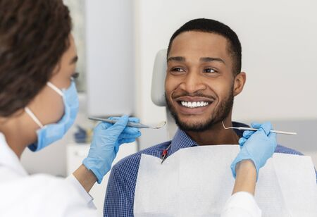 Smiling african guy in dentist chair looking with trust at his doctor, close up