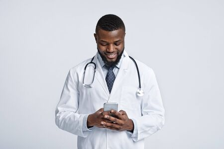 Stay in touch with your doctor during isolation. Cheerful african doctor using mobile phone over white studio background Stock Photo